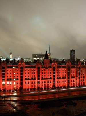 Bei einer Probebeleuchtung von Block V vor einem Jahr illuminierte Michael Batz die Speicherfassade statt im  gewohnten weißen Licht in einem warmen Rot, das durch den regnerischen Abendhimmel leuchtete.