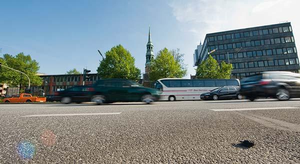 Die Baulücken an der Willy-Brandt-Straße sollen geschlossen werden. Der niedrige Backsteinbau der Schule wird durch einen Büroriegel ersetzt, das sechsstöckige Bürohaus rechts wird durch ein neues mit acht Geschossen ersetzt.