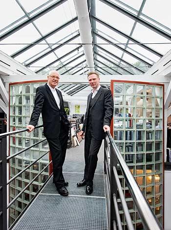 Alf M. Prasch (links) und Ekkehard Voss (rechts) in ihrem Büro, einem umgebauten Pferdestall am Stadtpark