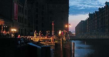 Eine Aufführung des Hamburger Jedermann vor dem Kesselhaus am Kehrwiederfleet. Mit der Abenddämmerung beginnt die Illumination und macht die Speicherstadt zur Bühne. (2)